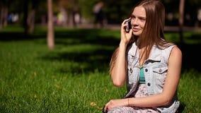 Donna che parla sullo Smart Phone all'aperto sull'erba archivi video