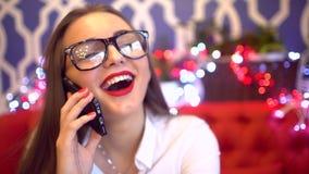 Donna che parla sullo Smart Phone che ride in caffè Bello giovane professionista femminile che ha conversazione casuale sul cellu archivi video