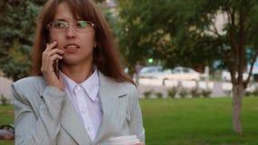 Donna che parla sullo smartphone e sul caffè bevente in parco la donna di affari con i vetri in un vestito leggero va lavorare archivi video