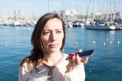 Donna che parla un massaggio di voce sul telefono Immagini Stock Libere da Diritti