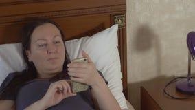 Donna che passa in rassegna il suo smartphone e che si trova a letto archivi video