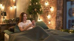 Donna che passa in rassegna media sociali sul cellulare a letto