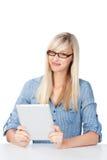 Donna che passa in rassegna sulla sua compressa Immagine Stock