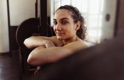 Donna che pende sopra il bilanciere dopo l'allenamento Fotografia Stock Libera da Diritti