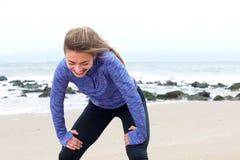Donna che pende sopra stare sulla spiaggia dopo l'allenamento Immagini Stock