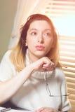Donna che pensa con i vetri dell'occhio a disposizione Fotografia Stock Libera da Diritti