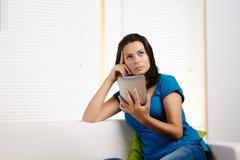 Donna che pensa mentre tenendo un PC del ridurre in pani Fotografia Stock Libera da Diritti