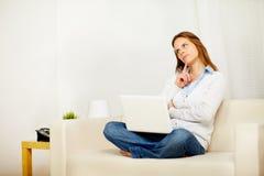 Donna che pensa sul sofà con un computer portatile Immagini Stock