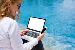 Donna che per mezzo dei dispositivi di tecnologia dallo stagno sulla vacanza immagini stock libere da diritti