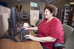 Donna che per mezzo del calcolatore delle biblioteche Immagine Stock