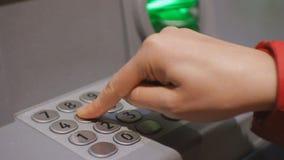 Donna che per mezzo del cash machine Codice entrante del perno della mano femminile sulla tastiera di BANCOMAT stock footage