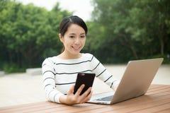 Donna che per mezzo del cellulare e del computer portatile fotografia stock
