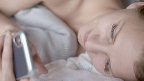 Donna che per mezzo del cellulare sul letto archivi video
