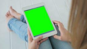 Donna che per mezzo del computer della compressa con lo schermo verde immagini stock