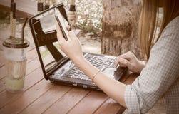 Donna che per mezzo del computer portatile Immagine Stock