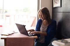 Donna che per mezzo del computer portatile Immagini Stock
