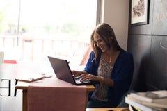 Donna che per mezzo del computer portatile Immagini Stock Libere da Diritti