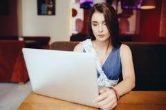 Donna che per mezzo del computer portatile alla caffetteria Fotografia Stock