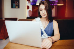 Donna che per mezzo del computer portatile alla caffetteria Fotografie Stock Libere da Diritti