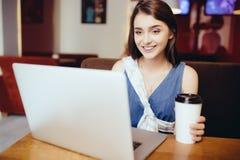 Donna che per mezzo del computer portatile alla caffetteria Fotografia Stock Libera da Diritti