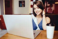 Donna che per mezzo del computer portatile alla caffetteria Fotografie Stock