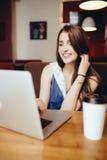 Donna che per mezzo del computer portatile alla caffetteria Immagine Stock