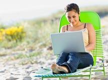 Donna che per mezzo del computer portatile alla spiaggia Fotografia Stock Libera da Diritti