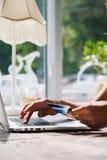 Donna che per mezzo del computer portatile con la carta di credito a disposizione Fotografia Stock