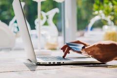 Donna che per mezzo del computer portatile con la carta di credito a disposizione Fotografia Stock Libera da Diritti
