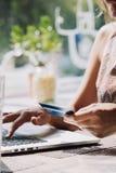 Donna che per mezzo del computer portatile con la carta di credito a disposizione Immagine Stock Libera da Diritti