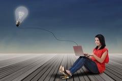 Donna che per mezzo del computer portatile con la lampadina all'aperto Fotografia Stock Libera da Diritti
