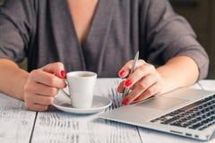 Donna che per mezzo del computer portatile con una tazza di caffè Immagini Stock Libere da Diritti