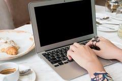 Donna che per mezzo del computer portatile con una tazza di caffè Fotografia Stock