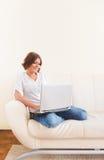 Donna che per mezzo del computer portatile e bevendo da una tazza Fotografia Stock Libera da Diritti