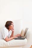 Donna che per mezzo del computer portatile e bevendo da una tazza Fotografie Stock Libere da Diritti