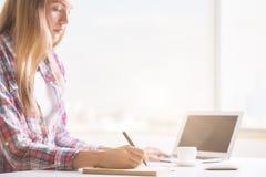 Donna che per mezzo del computer portatile e del blocco note Immagine Stock Libera da Diritti