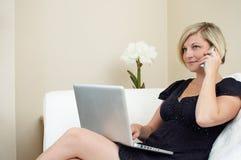 Donna che per mezzo del computer portatile e del telefono fotografia stock libera da diritti
