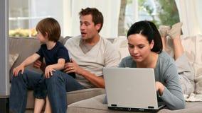 Donna che per mezzo del computer portatile mentre il suoi ragazzo e marito stanno guardando la TV stock footage