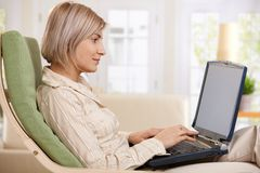 Donna che per mezzo del computer portatile nel paese Immagini Stock