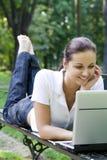 Donna che per mezzo del computer portatile sul banco all'aperto Fotografia Stock