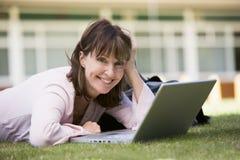 Donna che per mezzo del computer portatile sulla città universitaria Immagine Stock