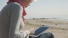 Donna che per mezzo del pc della compressa sulla spiaggia video d archivio