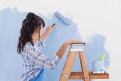 Donna che per mezzo del rullo di pittura per dipingere parete fotografia stock libera da diritti