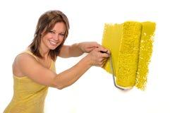 Donna che per mezzo del rullo di vernice con colore giallo Fotografia Stock Libera da Diritti