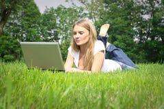 Donna che per mezzo del suo computer portatile Immagine Stock