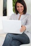 Donna che per mezzo del suo computer portatile Fotografia Stock