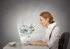 Donna che per mezzo del suo computer portatile che fa soldi Fotografie Stock Libere da Diritti