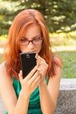 Donna che per mezzo del suo Smart Phone Fotografie Stock
