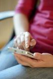 Donna che per mezzo del suo Smart Phone mobile a casa Immagine Stock Libera da Diritti