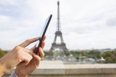 Donna che per mezzo del suo telefono cellulare davanti alla torre Eiffel Immagine Stock